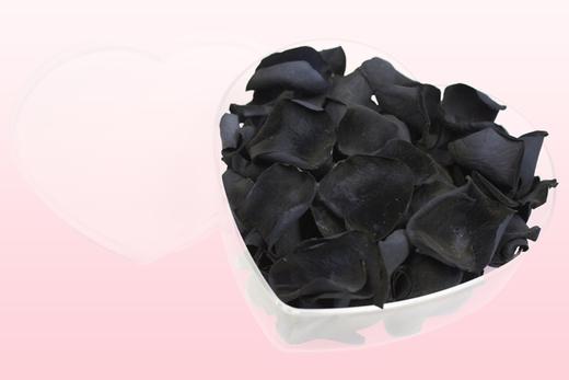 Cajita en forma de corazón con pétalos de rosa de color negro.
